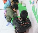 日托班老师一对一教小朋友写字
