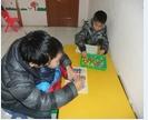 日托班生活自理站老师正在教小朋友系鞋带